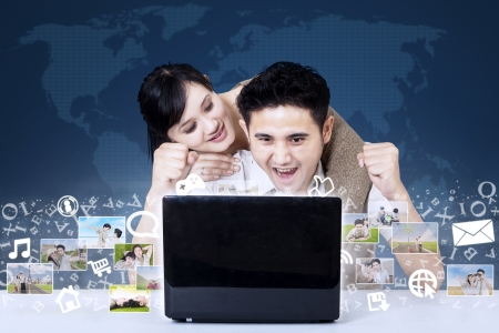 Excited Asian couple looking at digital photos on laptop with blue world map background Stock Photo - 21053244
