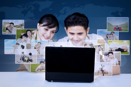 asian couple: Asian couple is looking at laptop to search digital photos worldwide on world map blue background Stock Photo