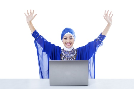 Happy female muslim in blue dress raised her arms with laptop on white photo