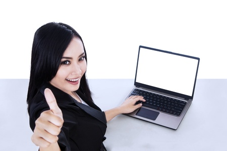 Businesswoman showing thumbs up with blank laptop on white photo
