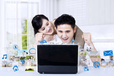 Asian couple looking at photo competition results at laptop at home Stock Photo - 21089775
