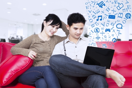 surfing the internet: Asian couple is surfing internet with laptop indoor Stock Photo