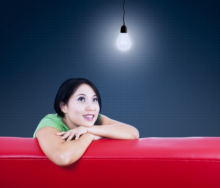 Asian female sitting on red sofa under lit bulb photo