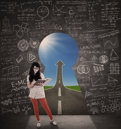 literatures: Asian female student reading book with success road view from keyhole Stock Photo