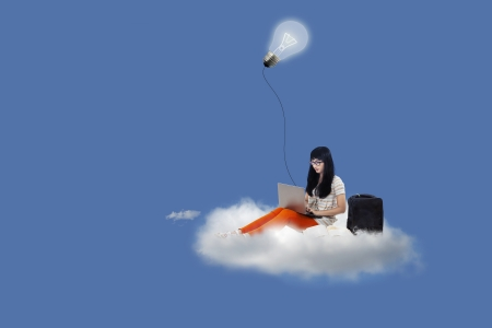 Asian female student typing on laptop with lamp and books above cloud photo