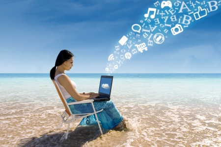 student travel: Asian woman with laptop working on the beach