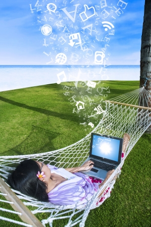 Asian woman using laptop on hammock at the beach with flying letters