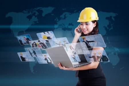 Beautiful female contractor is making a call and holding laptop on blue world map  photo
