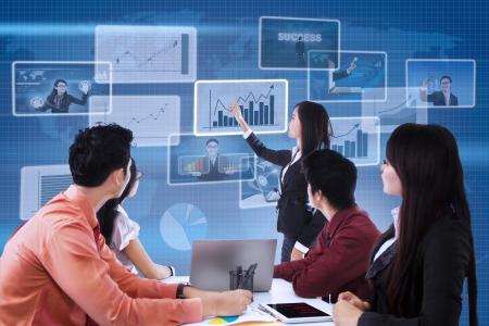 training: Business team is op zoek naar staafdiagram op een blauwe achtergrond van de wereldkaart Stockfoto