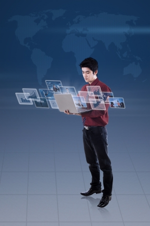 ultrabook: Businessman looking at pictures on laptop with blue world map background Stock Photo