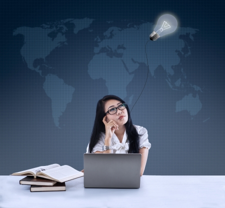Businesswoman with laptop and books thinking under lamp Stock Photo - 21089796