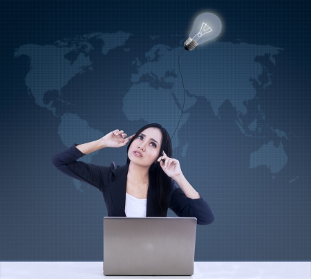 Businesswoman is thinking under lamp with laptop on blue world map background Stock Photo - 21089797
