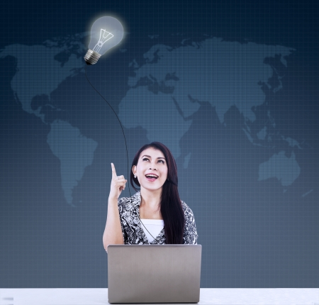 Businesswoman under lit bulb using laptop with world map background Stock Photo - 21089798