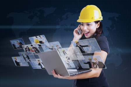 Excited contractor looking at pictures on laptop with blue world map background photo