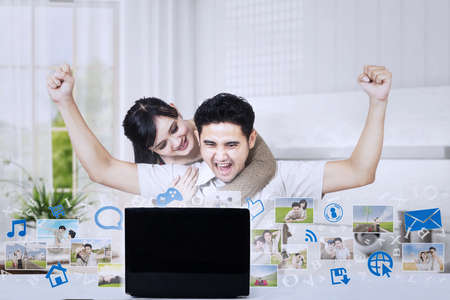 technology metaphor: Excited couple raised arms while looking at laptop with pictures at home