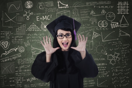 Excited female graduate with written blackboard in class