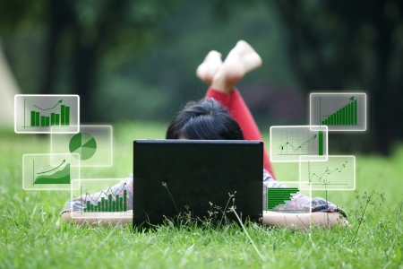 Attractive woman using laptop in the park lying on the green grass photo