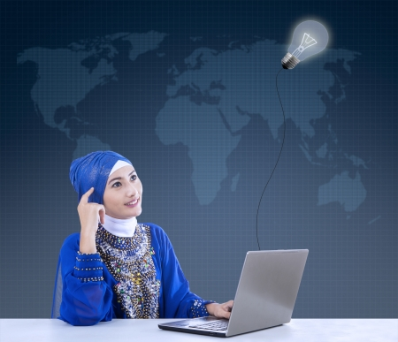 Female muslim in blue dress thinking under lamp while using laptop