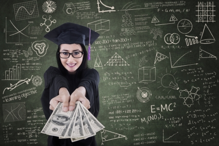 college graduate: Asian female graduate giving money in classroom - education cost concept