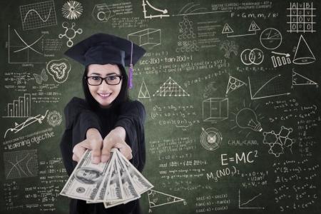 Aziatische vrouwelijke afgestudeerde geven geld in de klas - onderwijs kosten concept