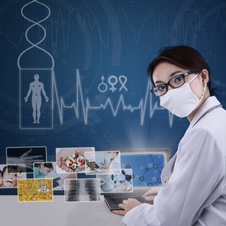 female scientist: Beautiful female scientist working in the lab with digital technology on blue background Stock Photo