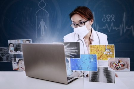 Female doctor writing prescription while looking at digital picture on her laptop with blue background photo