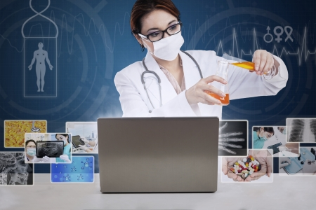 Beautiful female scientist is pouring yellow solution on blue background with digital pictures photo