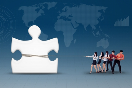 Business team is pulling a piece of puzzle on blue world map background photo