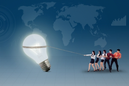 Business teamwork is pulling lit bulb on blue world map background photo