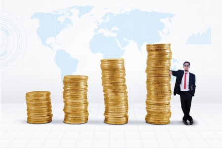Businessman standing next to gold coins chart on world map background photo