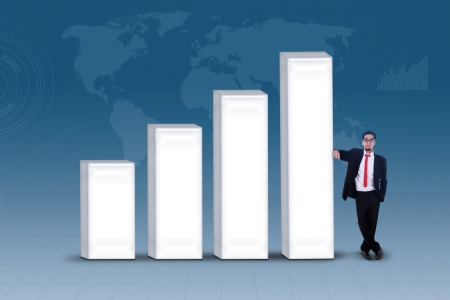 Businessman in black suit standing next to bar chart photo