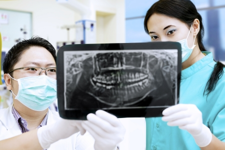 dentist mask: Dentist and beautiful assistant are analysing x-ray at dental clinic