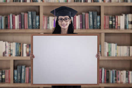 Happy graduation student girl with blank whiteboard in library photo