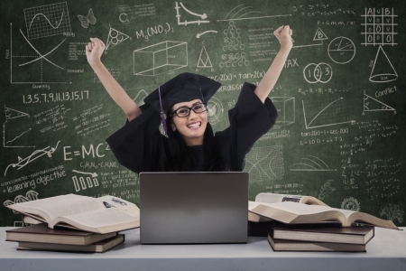 Cheerful graduate raised her arms with laptop and books in class photo
