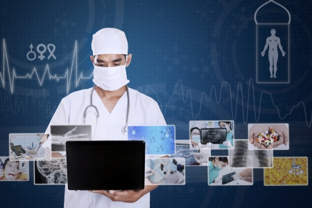 A medical healthcare doctor wearing a mask, stethoscope and typing on a computer laptop Stock Photo - 22632684