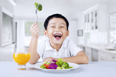 Cute little boy eats vegetable salad using fork, shot in the kitchen photo