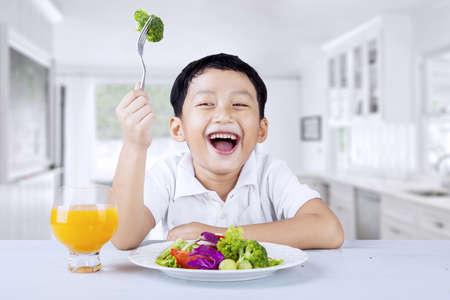 eten: Schattige kleine jongen eet fruit salade met vork, geschoten in de keuken Stockfoto