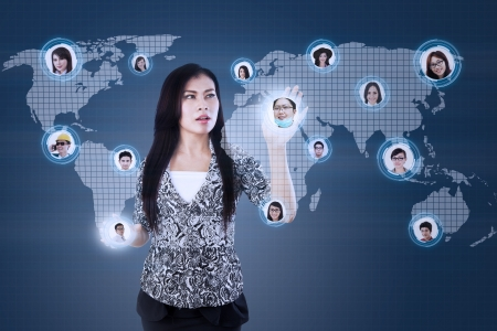 Beautiful businesswoman touch on workers head online with blue digital background photo