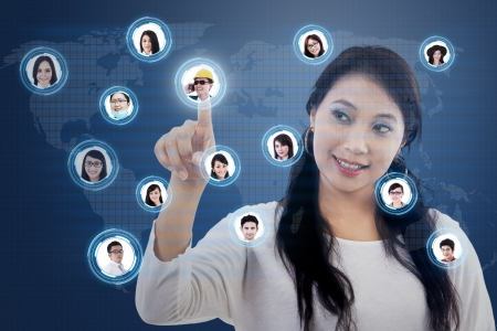 Beautiful female is clicking on one of people's head icon for networking purposes Stock Photo - 21380933