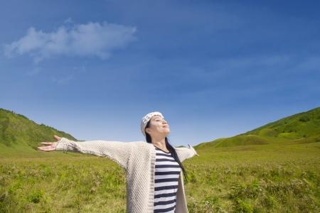 breeze: Beautiful female relaxing on green hills under blue sky