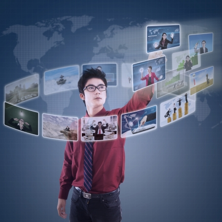 world connectivity: Businessman choosing on photo via digital touchscreen with world map background