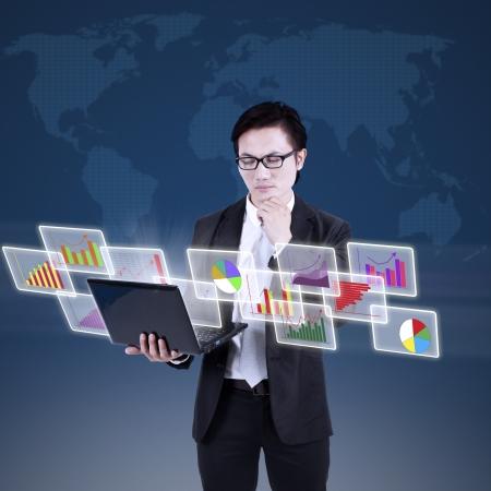 grafica de barras: Empresario busca en gr�ficos de barras en la computadora port�til con el fondo azul