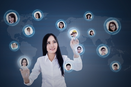 Young businesswoman connects with her team members using digital touchscreen Stock Photo - 21380957
