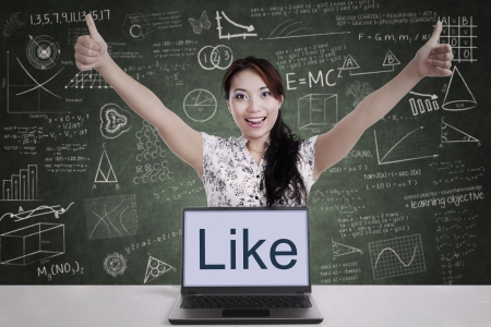 thumbsup: Successful businesswoman giving thumbs-up with laptop computer