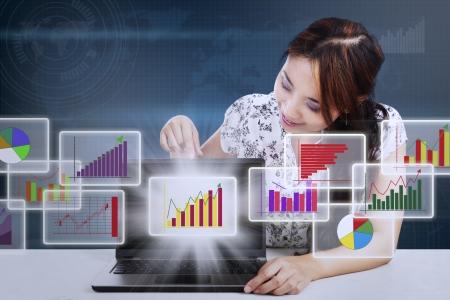 wartości: Businesswoman pokazano nowoczesny schemat analizy biznesowej i wykres z Internetu na komputerze przenośnym w Internecie komputerowej
