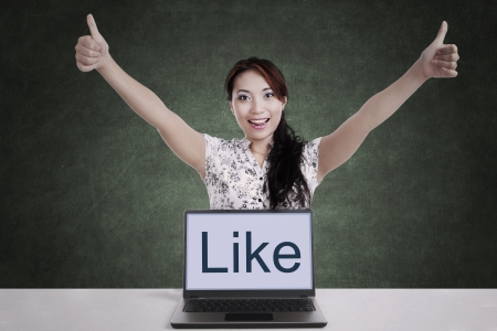 ultrabook: Successful businesswoman giving thumbs-up with laptop computer in class
