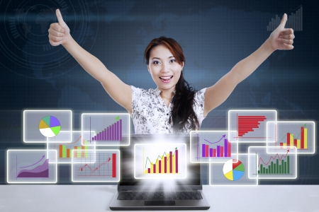 thumbsup: Successful businesswoman giving thumbs-up with different types of diagrams in 3d space Stock Photo