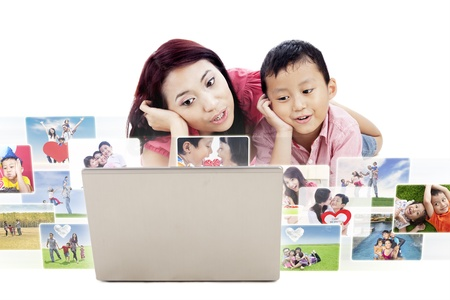 Cute mother and son are looking at digital photos on laptop, isolated on white photo