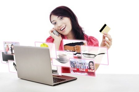 discounts: An attractive woman purchasing product online using her laptop computer, credit card, and mobile phone,  Stock Photo