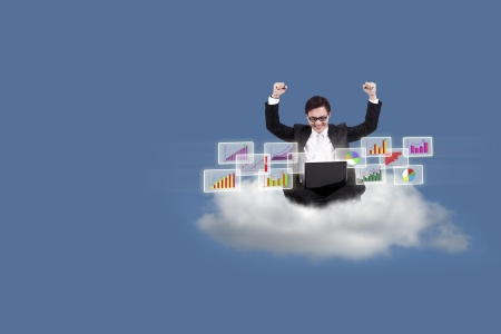 Cloud computing concept: Successful Asian businessman with laptop sitting on cloud Stock Photo - 21380973
